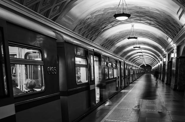 U-bahnwagen und plattform mit silhouetten von sich bewegenden menschen Premium Fotos