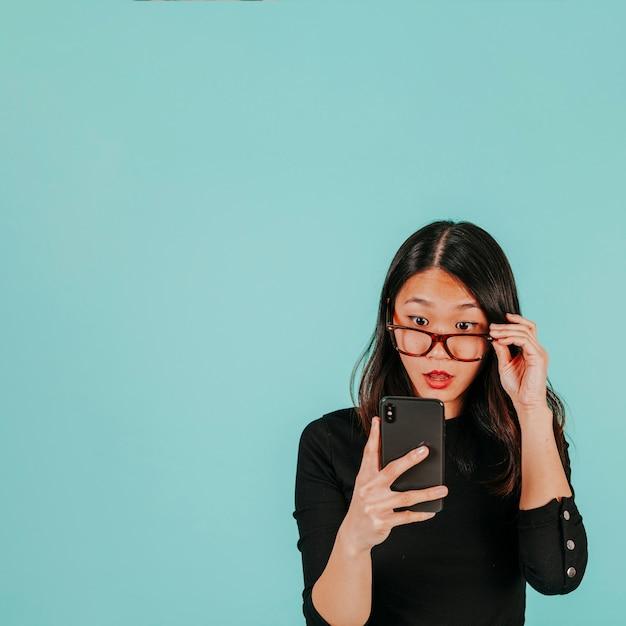 Überraschte Asiatin, die Smartphone betrachtet Kostenlose Fotos
