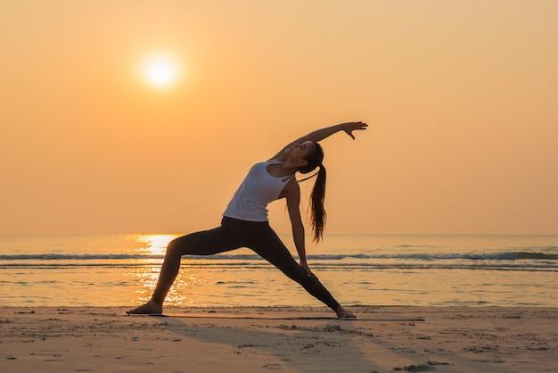 Übende yogahaltung der jungen gesunden yogafrau auf dem strand bei sonnenaufgang Premium Fotos