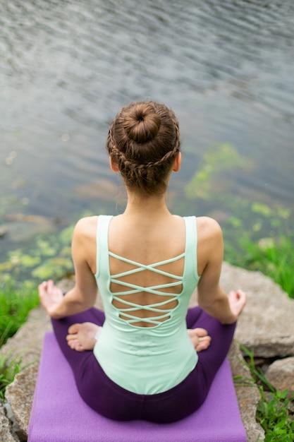 Übende yogalektion der yogafrau, atmung, meditation, übung ardha padmasana tuend, halbe lotoshaltung mit mudra geste, nahaufnahme im sommer auf natur gegen des wassers Premium Fotos