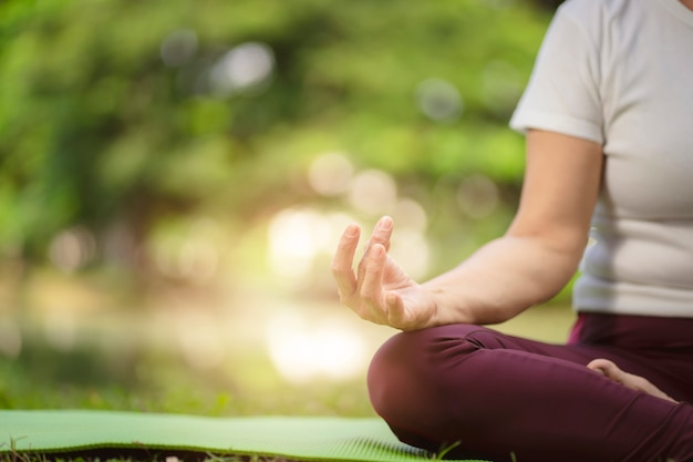Übende yogaübung der älteren asiatin im freien morgens. senior gesunden lebensstil Premium Fotos