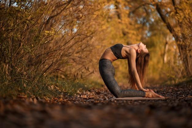 Übende yogaübung der jungen frau am herbstpark mit gelben blättern. sport und freizeit lifestyle Premium Fotos