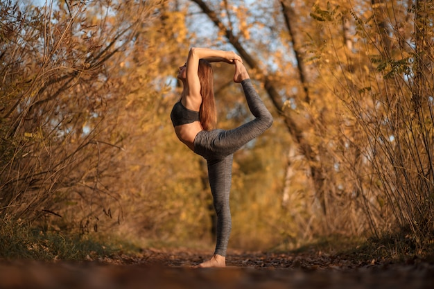 Übende yogaübung der jungen frau am herbstpark mit gelben blättern. Premium Fotos