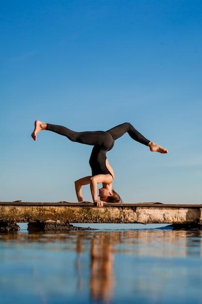 Übende yogaübung der jungen frau am ruhigen hölzernen pier mit stadt. sport und erholung in der großstadt Premium Fotos