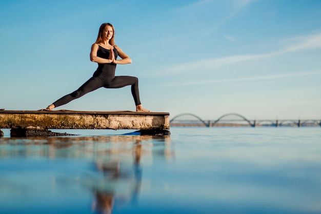 Übende yogaübung der jungen frau am ruhigen hölzernen pier mit stadt Premium Fotos