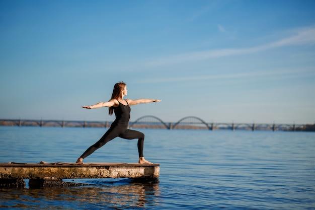 Übende yogaübung der jungen frau am ruhigen hölzernen pier mit stadthintergrund. sport und erholung in der großstadt Premium Fotos
