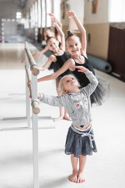 Übendes ballett des netten mädchens tanzen mit ihrer schwester im tanzstudio Kostenlose Fotos