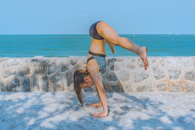 Übendes morgenyoga der jungen frau in der natur am strand. Premium Fotos