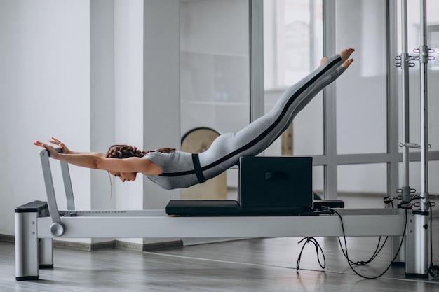 Übendes pilates der frau in einem pilates reformer Kostenlose Fotos