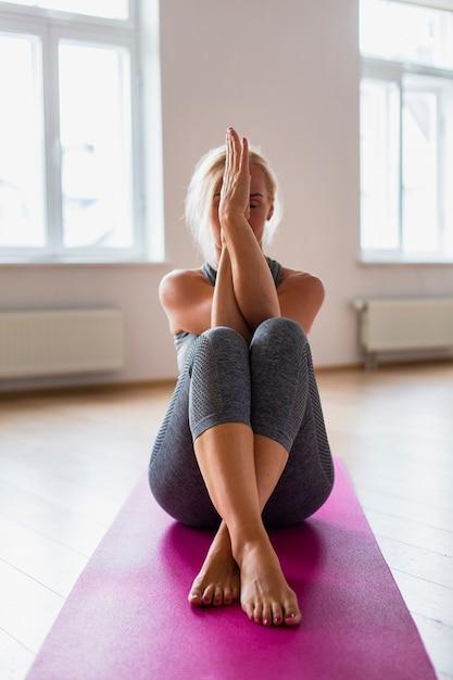 Übendes yoga der älteren frau in der sportkleidung Kostenlose Fotos