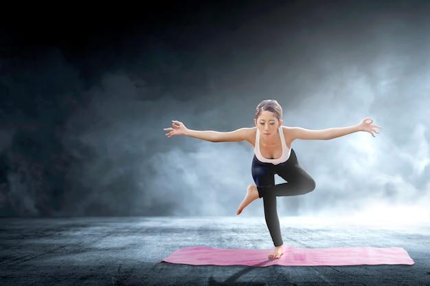 Übendes yoga der asiatischen gesunden frau auf dem teppich an innen Premium Fotos