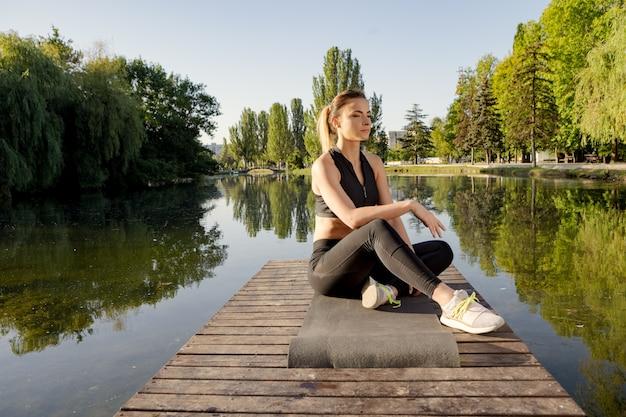 Übendes yoga der attraktiven frau auf einer matte auf einem pier nahe dem see morgens Premium Fotos