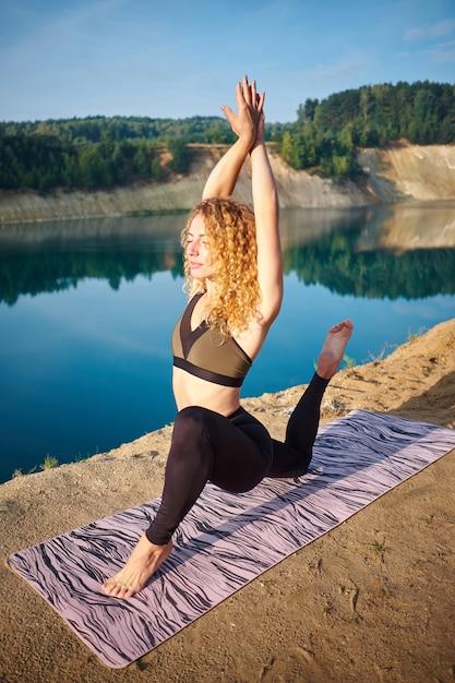 Übendes yoga der attraktiven gelockten frau der rothaarigen draußen Premium Fotos