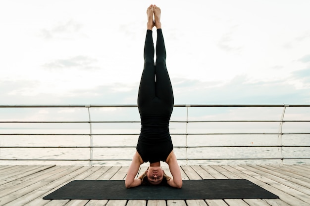 Übendes yoga der flexiblen frau und morgens stehen auf ihrem kopf in asana nahe dem meer auf sonnenaufgang, sport- und eignungsübungen tuend Premium Fotos