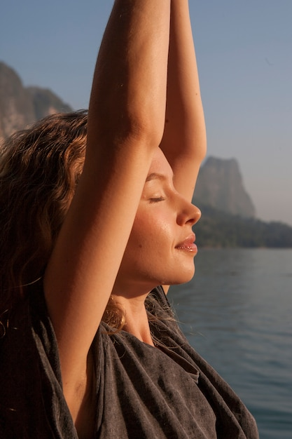 Übendes yoga der frau durch einen see Premium Fotos