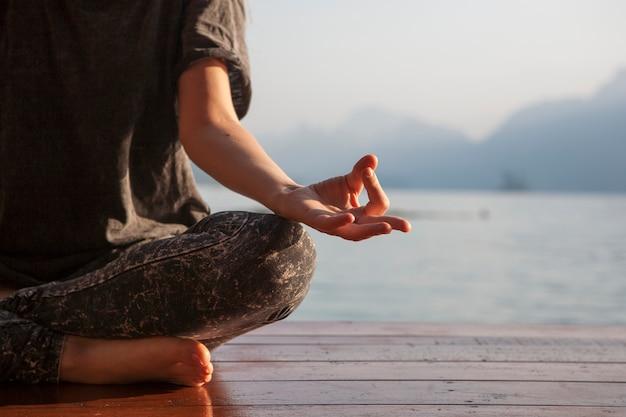 Übendes yoga der frau durch einen see Kostenlose Fotos