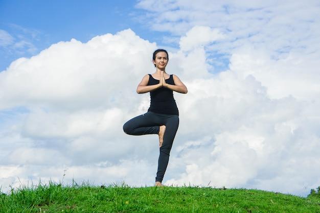 Übendes yoga der frau entspannen sich im hintergrund der natur und des blauen himmels Premium Fotos