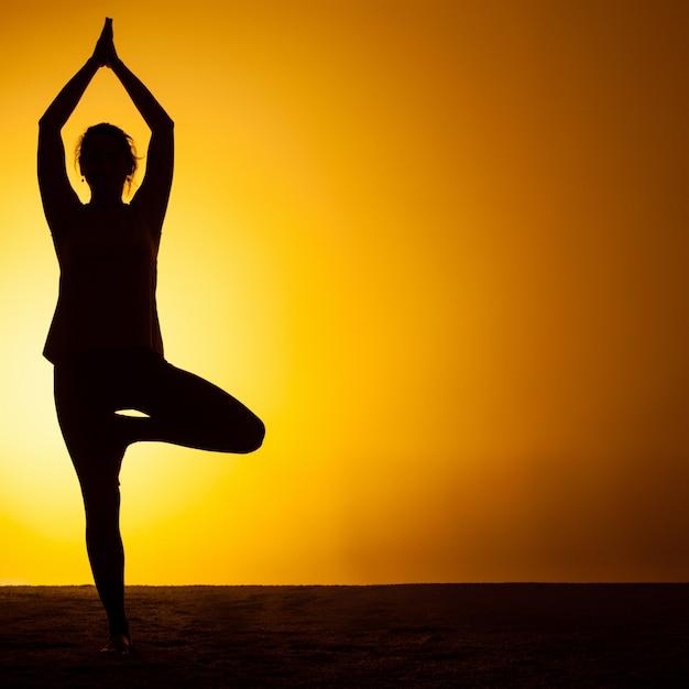 Übendes yoga der frau im sonnenunterganglicht Kostenlose Fotos