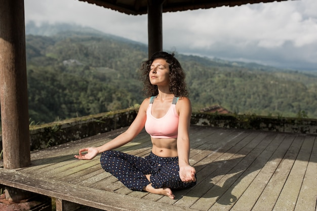 Übendes yoga der frau im traditionellen balinesse gazebo. Premium Fotos