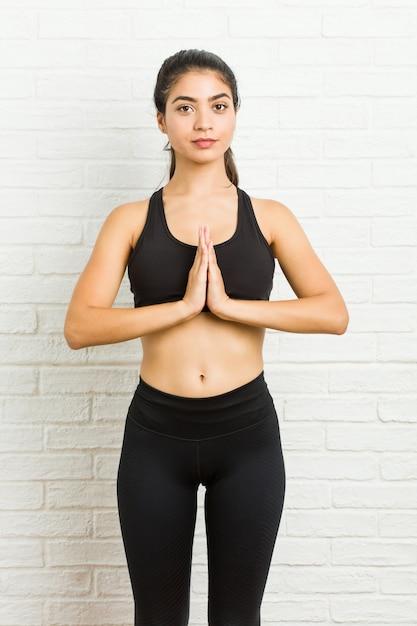 Übendes yoga der jungen arabischen sportlichen frau Premium Fotos