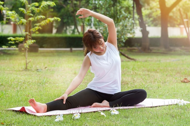 Übendes yoga der jungen asiatischen frau am abend im park Premium Fotos