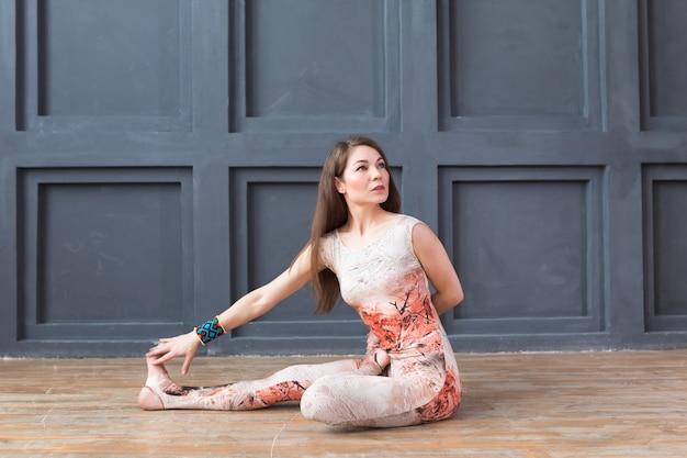 Übendes yoga der jungen attraktiven frau Premium Fotos