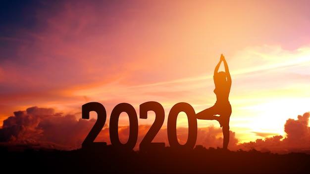 Übendes yoga der jungen frau des schattenbildes auf 2020 neuem jahr Premium Fotos