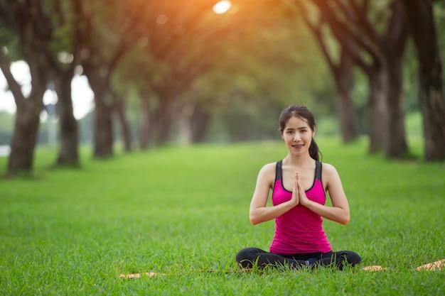 Übendes yoga der jungen frau im park Premium Fotos