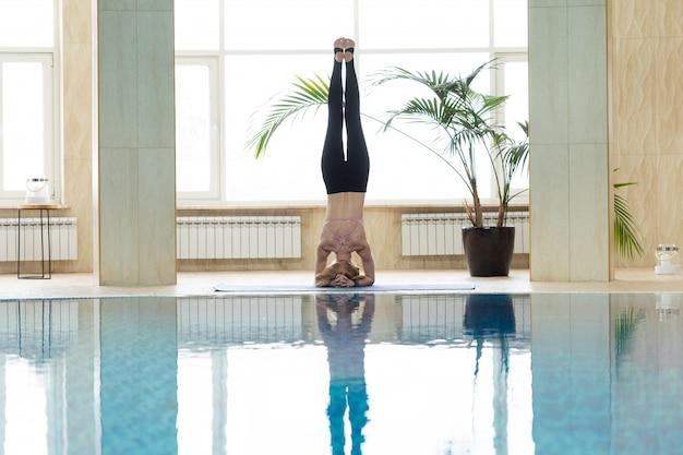Übendes yoga der jungen frau innen in der thermischen zone des swimmingpools. Premium Fotos