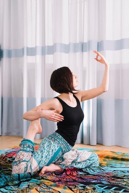 Übendes yoga der jungen frau mit mudra geste Kostenlose Fotos