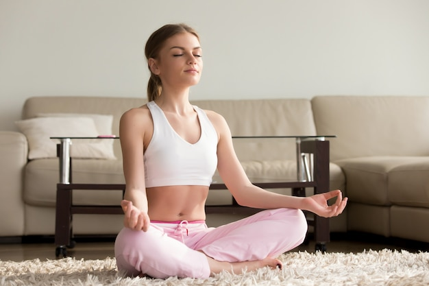 Übendes yoga der jungen frau zu hause Kostenlose Fotos
