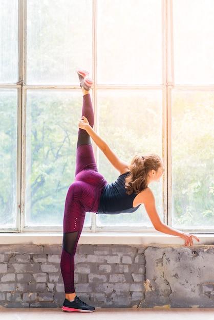 Übendes yoga der jungen geschäftsfrau der eignung nahe dem fenster Kostenlose Fotos