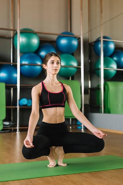 Übendes yoga der jungen sportlichen attraktiven frau in der turnhalle Kostenlose Fotos