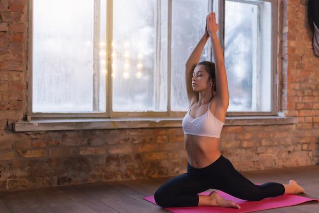 Übendes yoga der jungen sportlichen frau nahe dem fenster Premium Fotos
