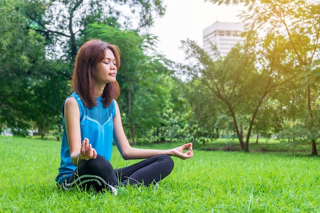 Übendes yoga der jungen und schönen asiatischen frau draußen im park mit grünem natur backgro Premium Fotos