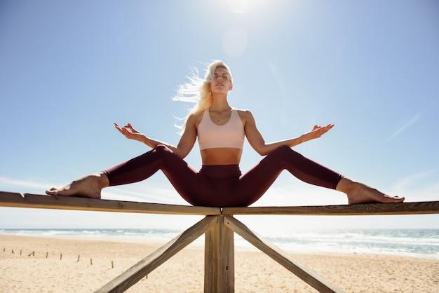 Übendes yoga der kaukasischen blondine im strand Premium Fotos