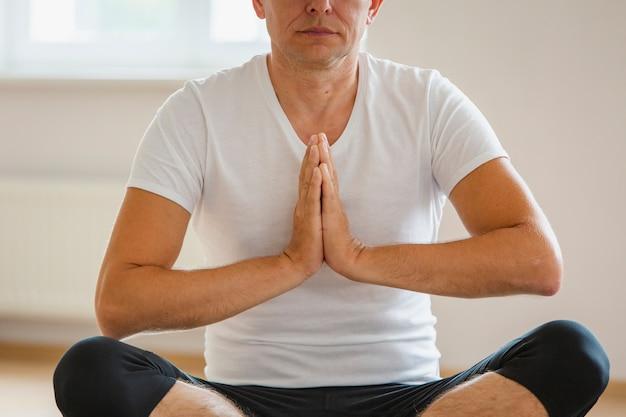 Übendes yoga der nahaufnahme erwachsener mann Kostenlose Fotos