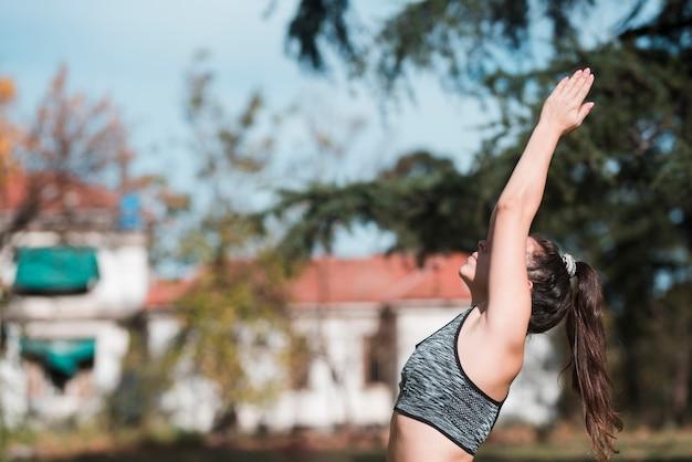 Übendes yoga des entspannten mädchens im freien Kostenlose Fotos