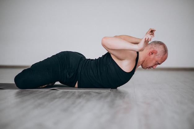 Übendes yoga des mannes in der turnhalle Kostenlose Fotos