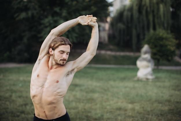 Übendes yoga des sportlichen mannes im freien Premium Fotos