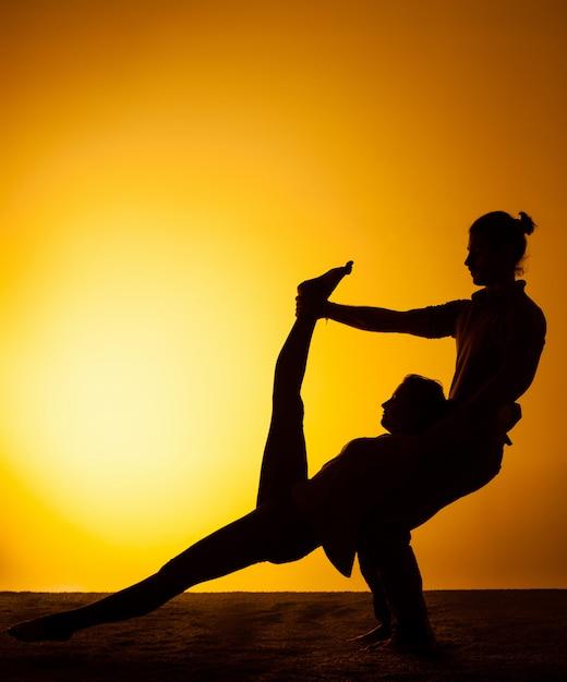 Übendes yoga von zwei leuten im sonnenunterganglicht Kostenlose Fotos