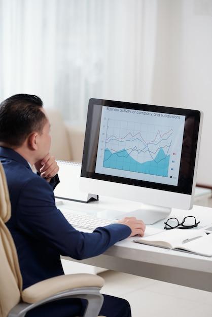 Über der schulteransicht des unternehmers das geschäftsdiagramm auf dem schirm seines tischrechners analysierend Kostenlose Fotos
