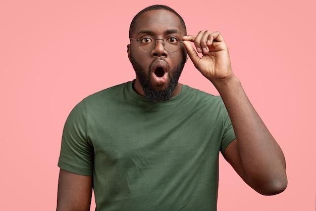 Über emotionale dunkelhäutige schockierte unrasierte afroamerikaner starrt mann durch brille, hält den kiefer fallen Kostenlose Fotos