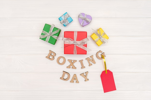 Über geschenkboxen wird mit einem band mit wörtern boxing day und rotem tag auf hölzernem weißem hintergrund gebunden Premium Fotos