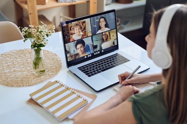 Über schulteransicht des studentenmädchens in den kopfhörern, die am tisch sitzen und an der online-konferenz in der studentengruppe teilnehmen Premium Fotos