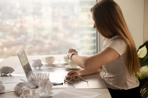 Überarbeitete geschäftsfrau, die armbanduhr, zeit überprüfend betrachtet, um frist einzuhalten Kostenlose Fotos