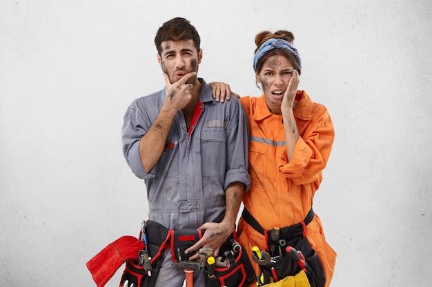 Überarbeiteter unglücklicher bärtiger handwerker und seine assistentin, Kostenlose Fotos