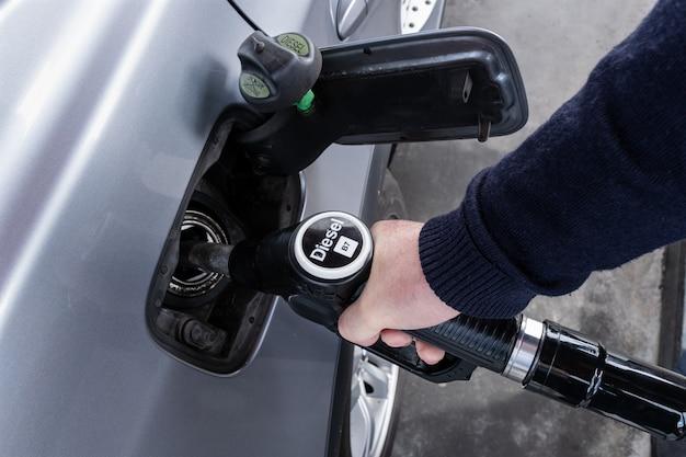 Übergeben sie das halten der dieseldüse für das betanken des autos an der tankstelle Premium Fotos