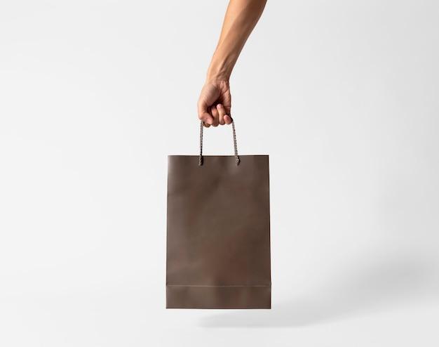 Übergeben sie das halten der leeren braunen papiertüte für modellschablonenwerbung und -branding auf grauem hintergrund. Premium Fotos