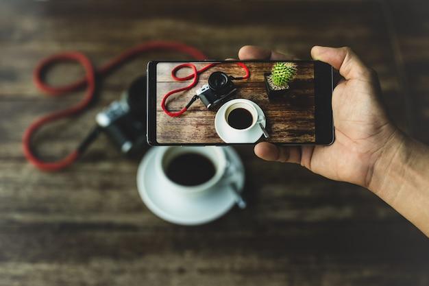Übergeben sie das halten des intelligenten telefons, das foto des kaffees und der kamera auf holztisch macht. Premium Fotos